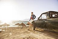 Greece, Crete, Matala, woman leaning against pickup truck at the beach - CHPF000077