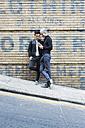 China, Hong Kong, gay couple at house wall looking on cell phone - JUBF000001