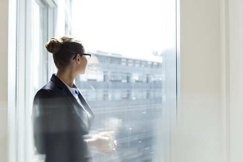 Businesswoman looking out of window - WESTF020953