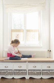Little girl playing recorder at home - OPF000046