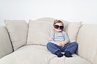 Little boy with oversized sunglasses sitting on couch - OPF000038
