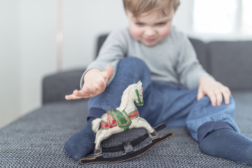 Little boy playing with wooden rocking horse - OPF000041