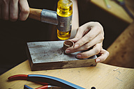 Goldsmith working with rubber mallet on wedding rings - KRPF001309