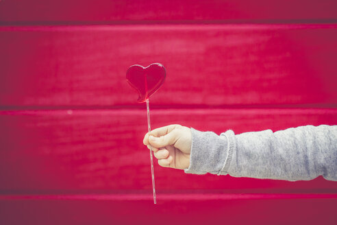 Close-up of boy holding heart-shaped lollipop in front of red wall - SARF001433