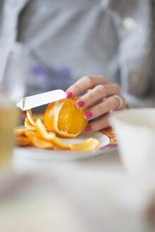 Woman peeling orange - CHPF000081