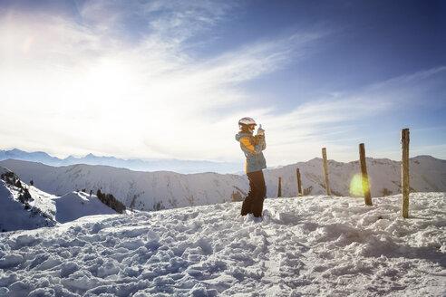 Austria, Salzburg State, Hochkoenig Region, young female skier taking picture with smartphone - DISF001424