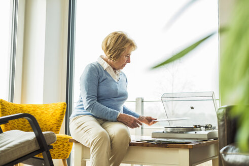 Senior woman at home putting record on record player - UUF003469