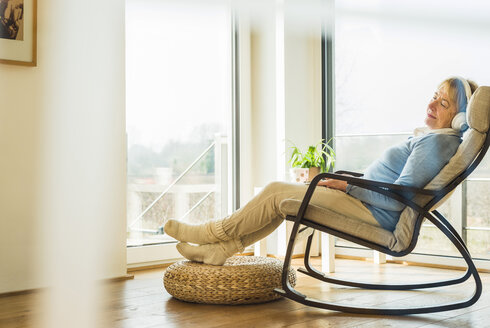 Senior woman at home relaxing with headphones - UUF003476