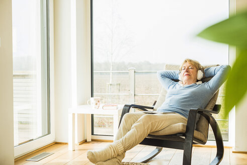 Senior woman at home relaxing with headphones - UUF003478