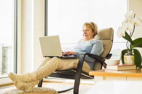 Senior woman at home using laptop - UUF003480