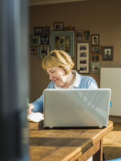 Senior woman at home with laptop and notebook - UUF003484