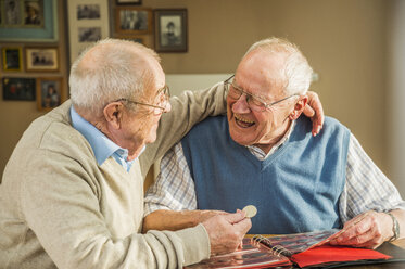 Two happy senior friends with coin album - UUF003536