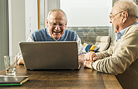 Two senior friends looking at laptop - UUF003550