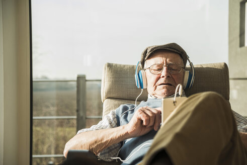 Senior man at home relaxing with headphones - UUF003552