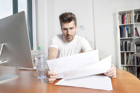 Young man watching documents at desk in an office - PATF000043