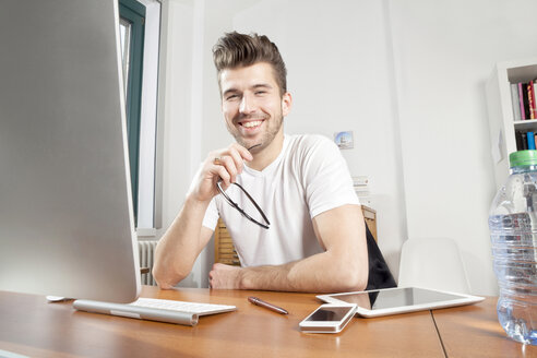 Portrait of smiling young man at desk in an office - PATF000045