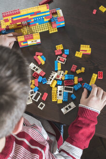 Boy playing with building bricks on a table - DEGF000370