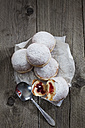 Five Bismarck doughnuts on paper and grey wood - CSF024676