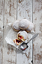 Four Bismarck doughnuts on paper and grey wood - CSF024677