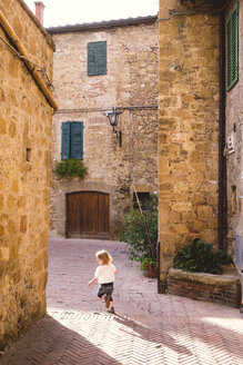 Italy, Tuscany, Pienza, Little girl running through lane in historic old town - GSF000953