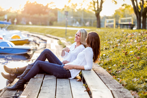 Two female friends sitting on boardwalk - DAWF000263