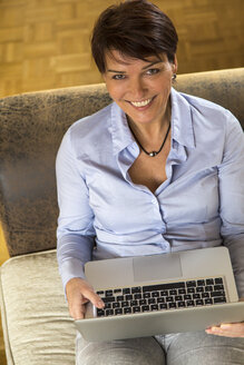 Mature woman sitting on couch using laptop - JFEF000619