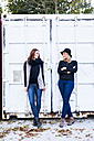 Two female friends standing in front of a container - DAWF000295