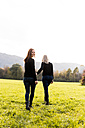 Lesbian couple walking hand in hand on a meadow - DAWF000299
