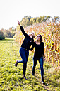 Happy lesbian couple walking along a cornfield - DAWF000301