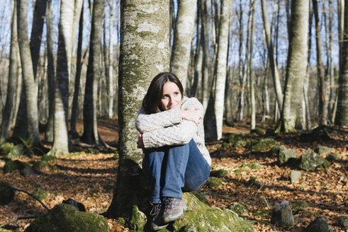 Woman sitting on a rock in a beech forest - GEMF000071