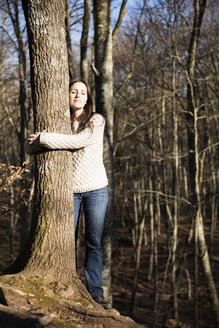 Woman hugging a beech tree in the forest - GEMF000073