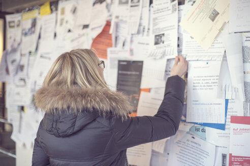 Woman reading at notice board - CHPF000092