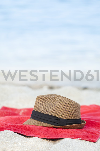 Towel and straw hat on sandy beach - BZF000060