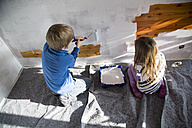 Brother and sister painting wooden wall - SARF001443