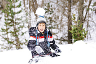 Happy boy throwing a snowball in the woods - GEMF000088