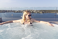 Spain, Menorca, Es Castell, blond woman relaxing in whirlpool on roof terrace - CHP000094