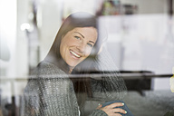 Smiling woman looking through window - SHKF000271