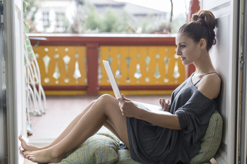 Young woman using laptop on balcony - SHKF000287