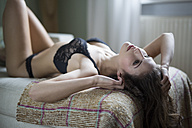 Sensual young woman in lingerie lying on couch - SHKF000295