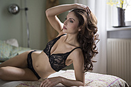 Sensual young woman in lingerie lying on couch - SHKF000297