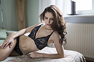 Sensual young woman in lingerie lying on couch - SHKF000299