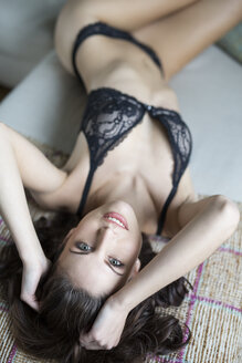 Sensual young woman in lingerie lying on couch - SHKF000300