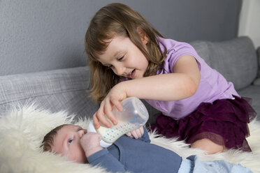 Little girl feeding newborn brother with baby bottle - ROMF000058