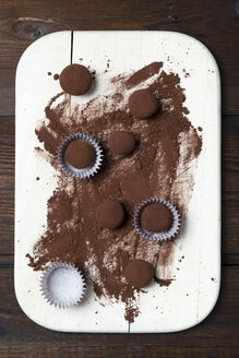 Chocolate truffles and cocoa powder on wooden board - MYF000904
