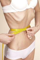 Anorexic young woman measuring her waist - DRF001493