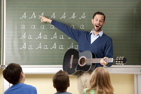 Teacher with guitar at blackboard showing variations of letter A - MFRF000110