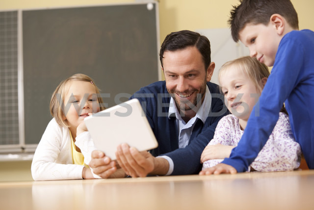 Teacher with pupils using digital tablet in classroom - MFRF000099
