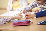 Pupils handing over slip of paper in classroom - MFRF000152
