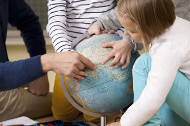 Teacher and pupils pointing at globe in classroom - MFR000134