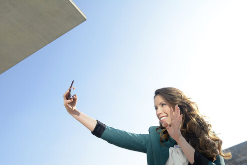 Smiling businesswoman taking selfie under blue sky - BFRF000988